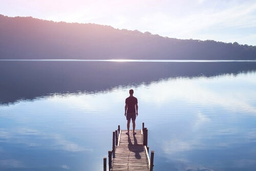 man standing on a dock over a lake to step out of his comfort zone