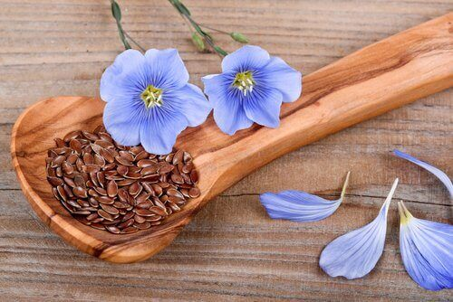 Flaxseeds in a wooden spoon with purple flowers as decoration edible seeds