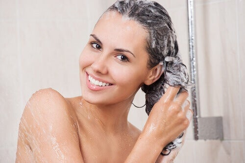 woman washing her hair with shampoo for personal hygiene