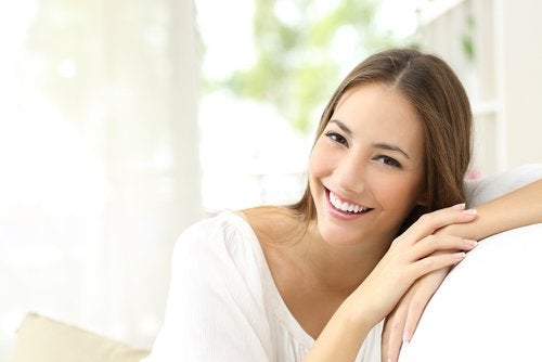A woman smiling with healthy skin from ginger and carrot juice.