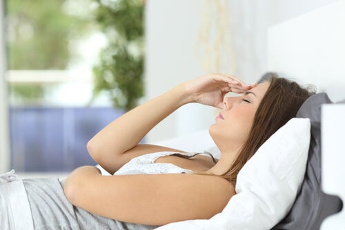 woman lying in bed with stress headache pain