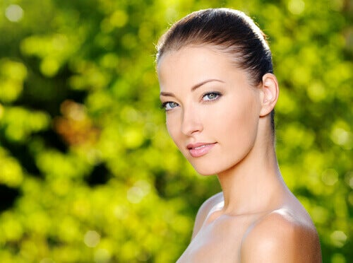Woman with beautiful glowing skin with green leaves background benefits of fish oil