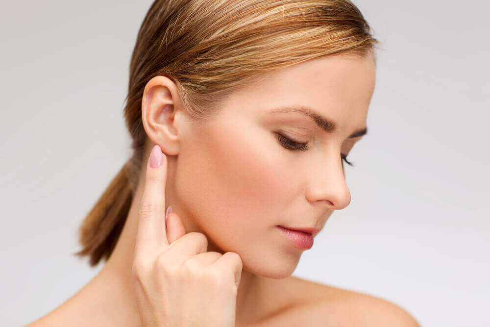 A woman pointing to her ear.
