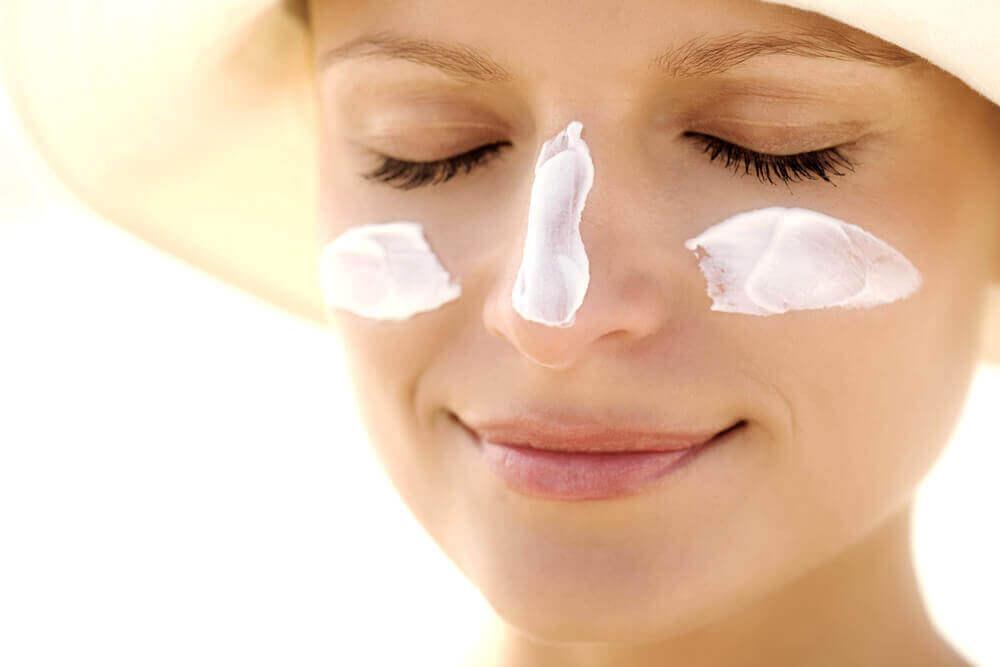 A woman using sunscreen.