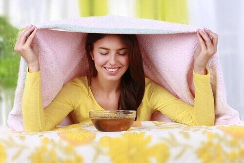 Woman with a steam bath and pink towel to clear her sinuses.