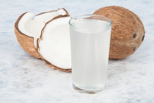 A cut coconut and glass of coconut milk.
