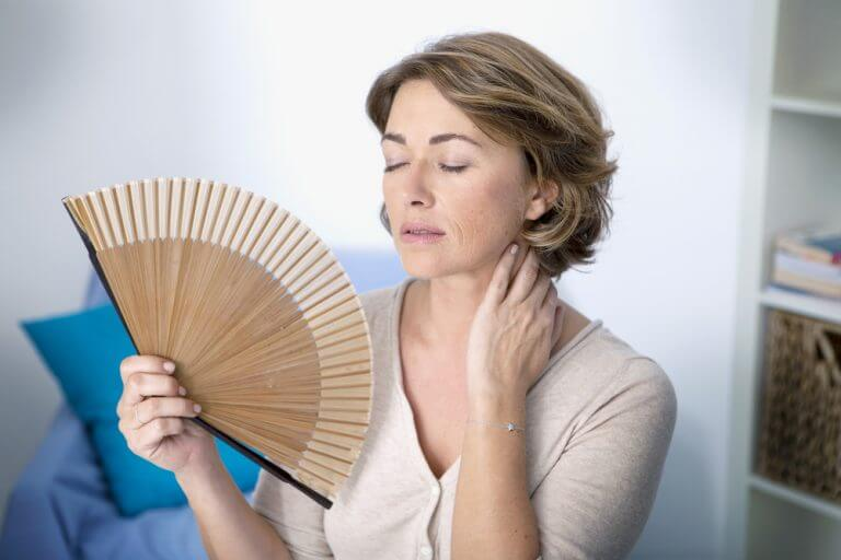 woman fanning herself indoors during menopause