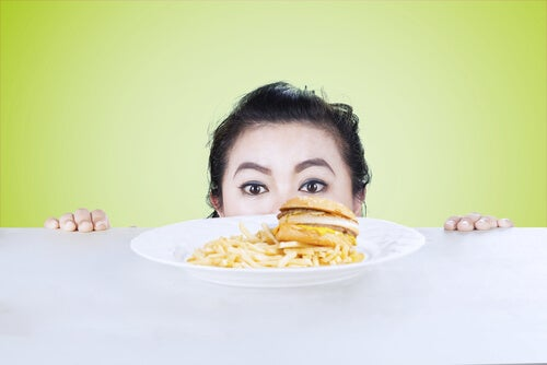 woman looking at a burger and fries