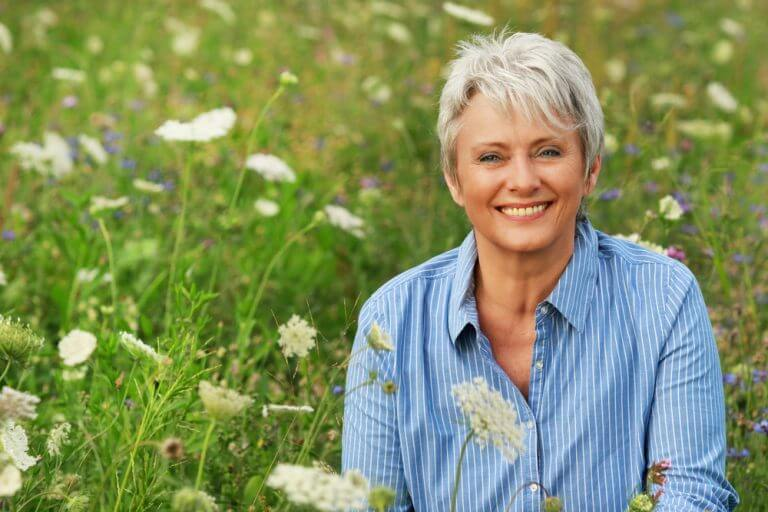 woman in a field of flowers finding happiness during menopause