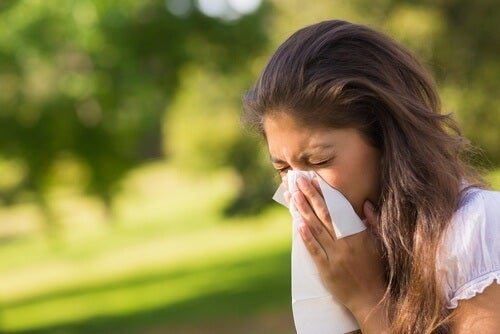 A woman sneezing due to her allergies.