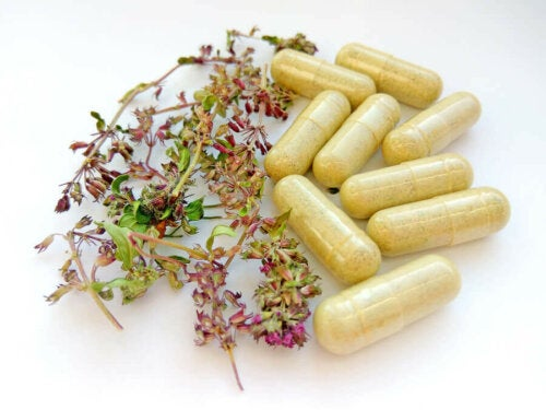 capsules of medicinal plants medication on a table next to flowers