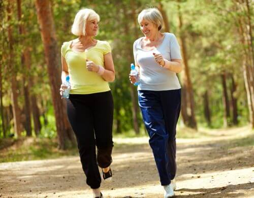 Two women in the woods who are walking to lose weight.