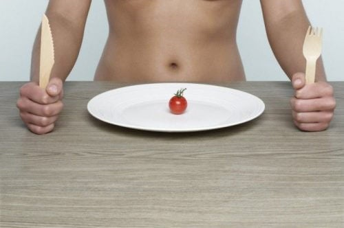 naked person with a plate and tomato