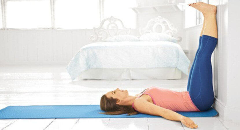 Woman doing yoga at home benefits of elevating your legs