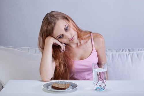 woman with loss of appetite looking at toast and water