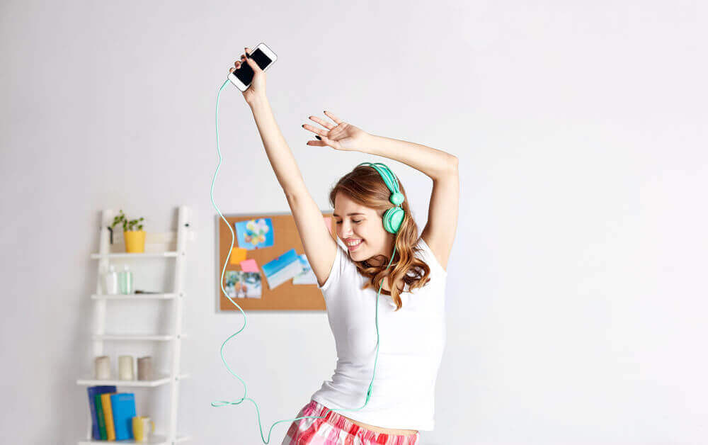 A woman dancing in her home while wearing headphones.