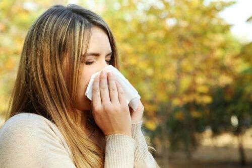 Kvinna med säsongsallergier snyter sig