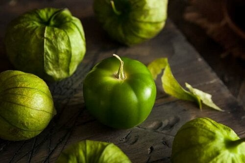 A naked tomatillo surrounded by properly dressed ones.
