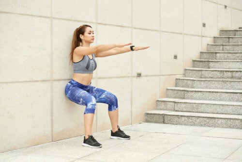 A woman with hard abs doing exercise against the wall.