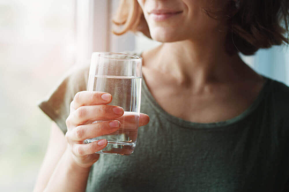 A woman hydrates with a glass of water.