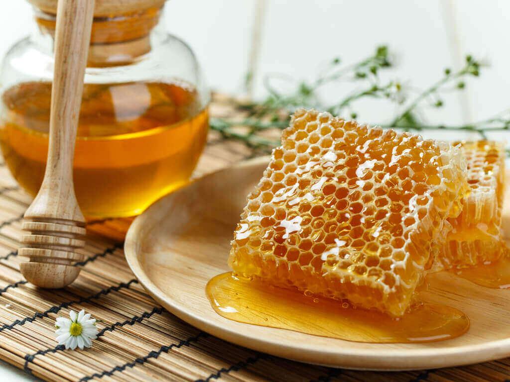 A jar of honey and a honeycomb.