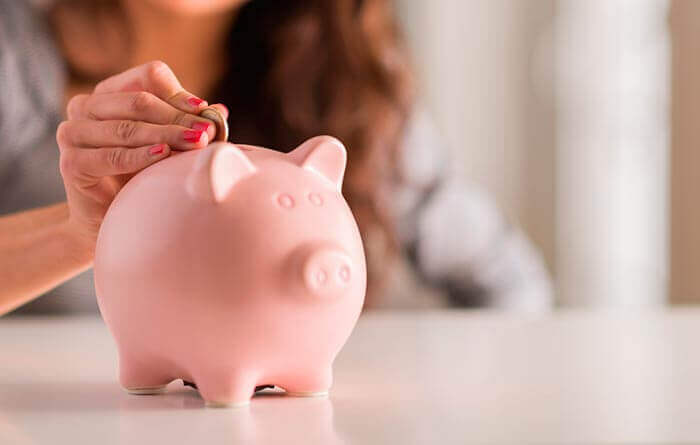 a woman putting money in a piggy bank to save money