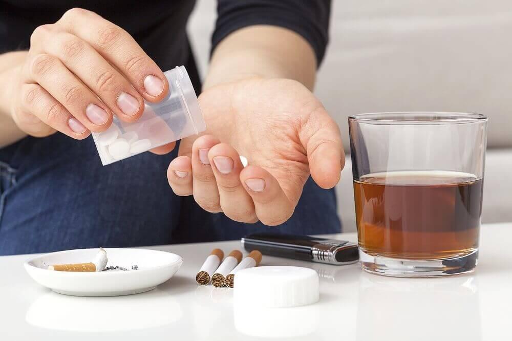 Een persoon drinkt alcohol, rookt, en slikt pillen