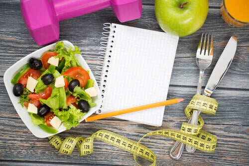 a salad, tape measure, silverware, and a notebook to represent nutrition advice