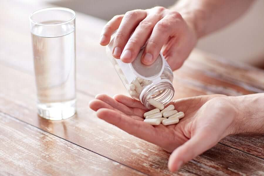 A person pouring pills into their hand.