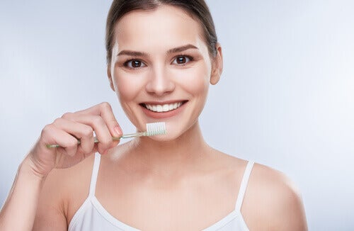 woman brushing teeth with coconut oil toothpaste
