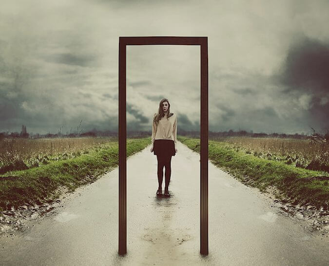 A girl facing a mirror on a road.