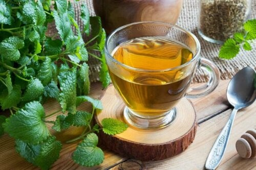 A cup of tea beside some mint leaves.