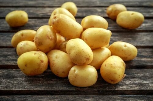 A pile of potatoes on a wooden table.