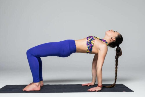 A woman in the bridge pose which is good for toning your legs.
