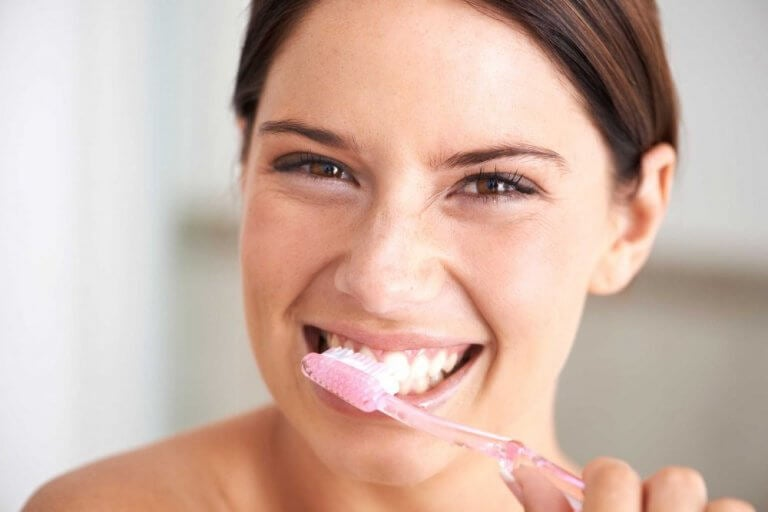 a woman smiling and brushing her teeth