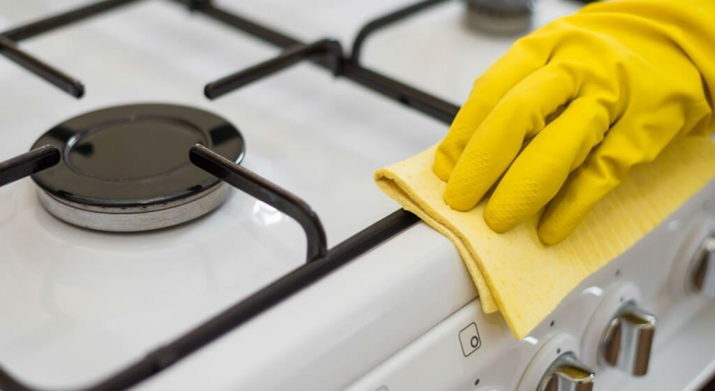 A person cleaning their kitchen with yellow gloves.