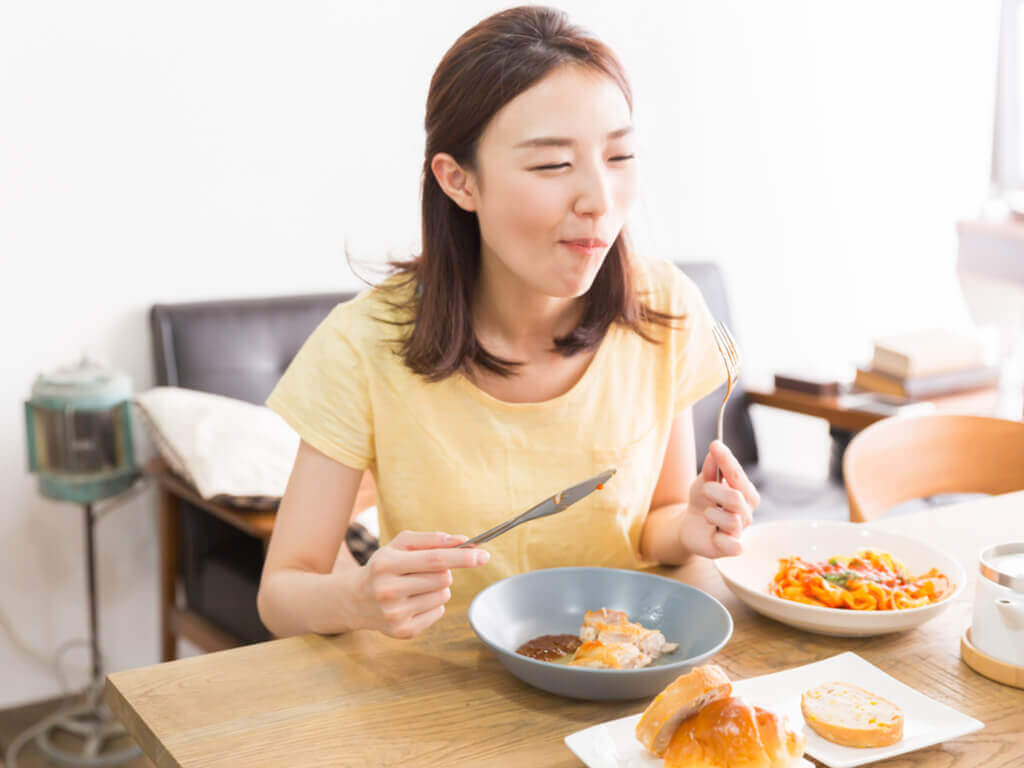 A woman eating breakfast at the table after intermittent fasting.