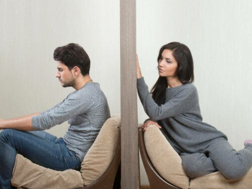 a woman looking at her partner, with him looking away, representing a loveless relationship