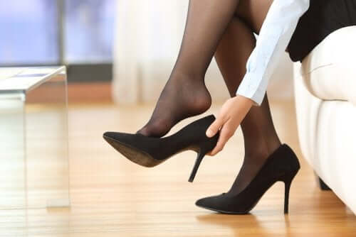 A woman putting on her high heels.