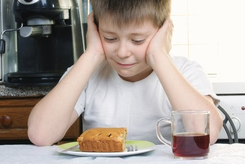 child looking sadly at a plate of food