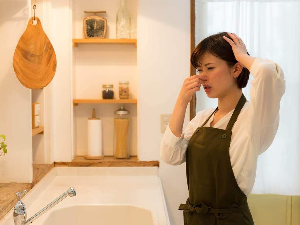 a kitchen that smells badly and a woman plugging her nose because of the odor