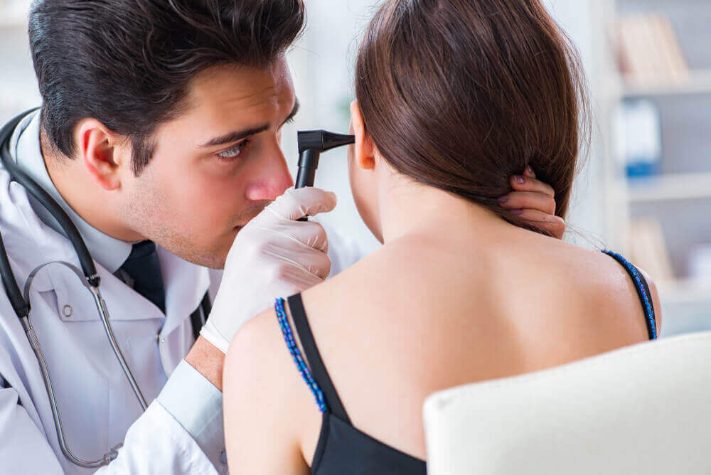 A doctor examining a woman's ear.