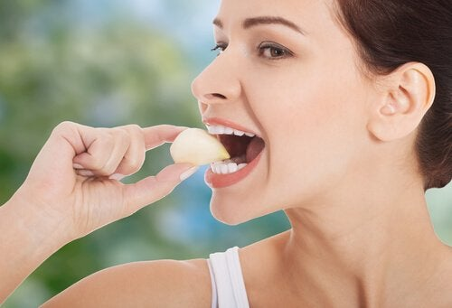 woman eating a garlic clove to help treat hypertension