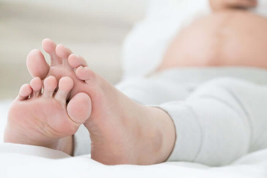 The feet of a pregnant woman who's lying in bed.