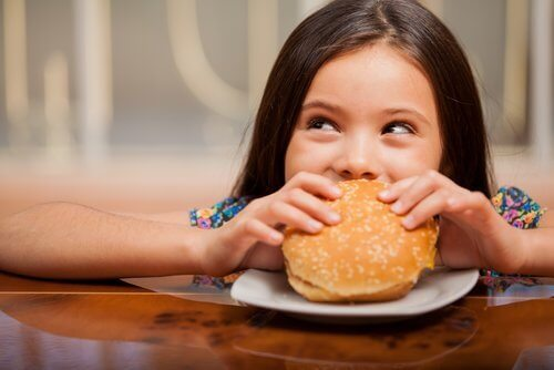 girl happily eating hamburger