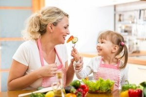 mother and daughter laughing and eating fruits and vegetables