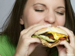 woman eating cheeseburger with her eyes closed