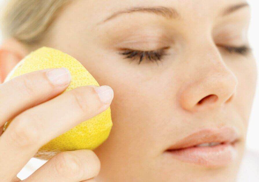 Woman using lemon to prevent wrinkles.