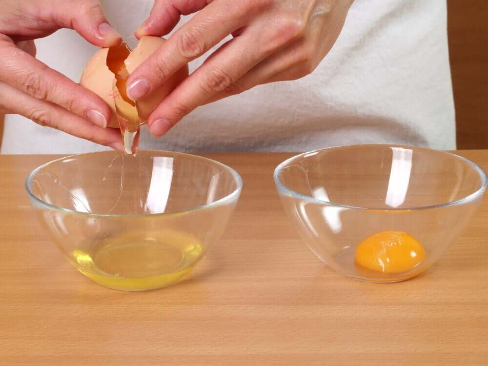 A woman cracking an egg and separating the yolk.