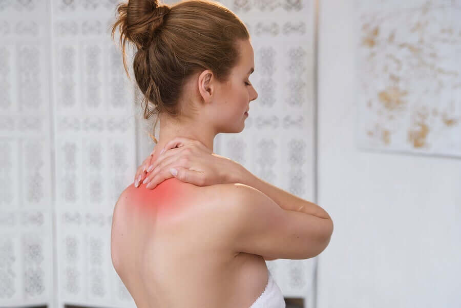 A woman with her hands on the back of her neck.
